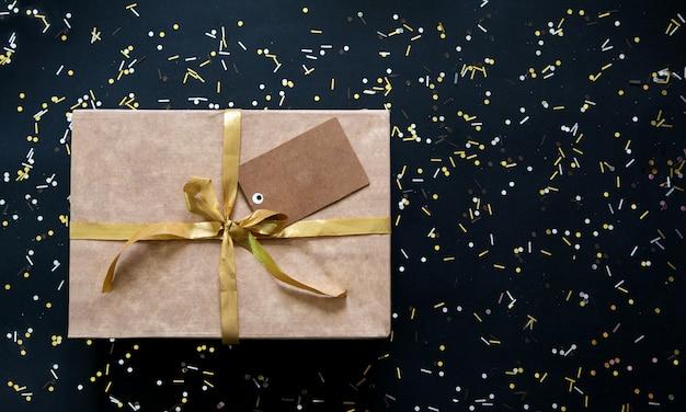 Shopping noir et doré avec cadeau et étiquette