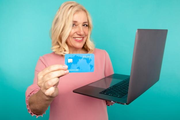 Shopping sur ordinateur. femme souriante avec ordinateur portable et carte de crédit faisant des achats en ligne.