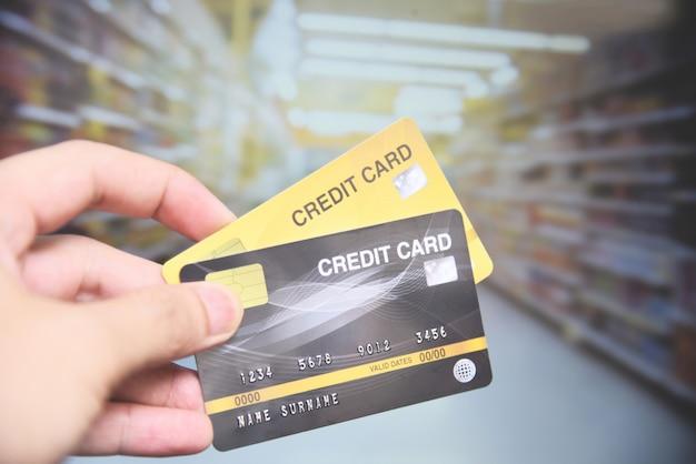 Shopping par carte de crédit au supermarché - main tenant le paiement par carte de crédit