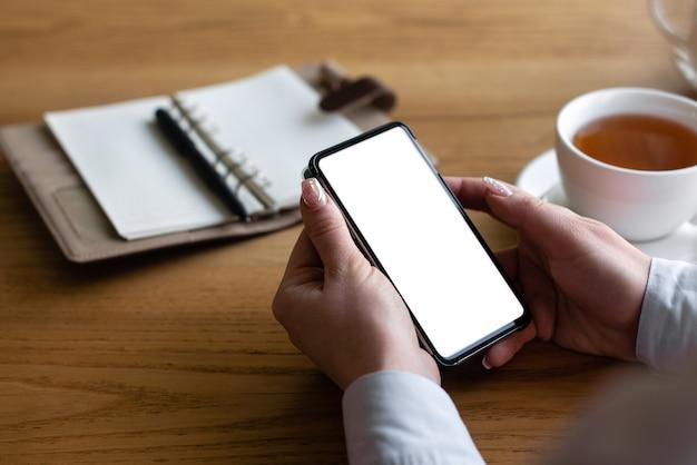 Shopping par téléphone, la jeune femme s'assoit à la maison et passe une commande de marchandises sur internet pour cela utilise un smartphone.