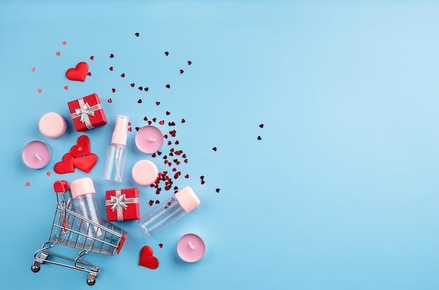 Shopping de la saint-valentin. panier avec divers produits cosmétiques, étiquette de prix, vue de dessus de confettis à plat sur fond bleu