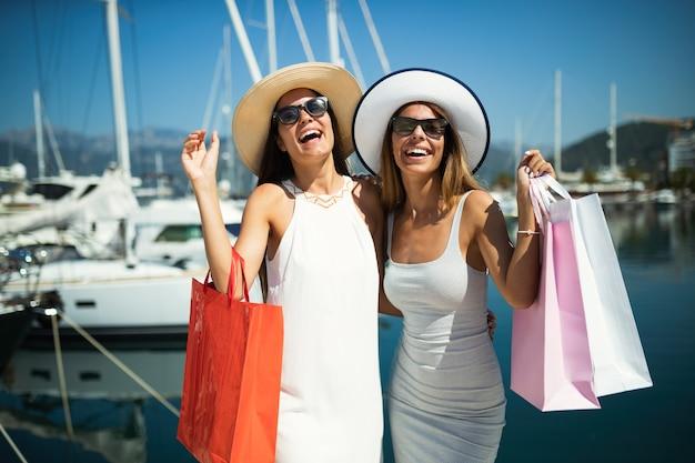 Shopping et tourisme, vacances, heureux, amis, concept de personnes. belles femmes avec des sacs à provisions en été