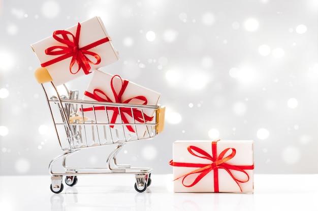 Shopping de vacances. mini panier avec des cadeaux sur fond blanc avec des lumières.