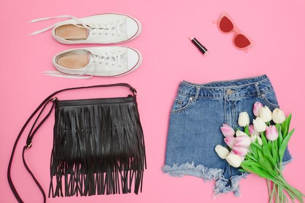 Short en jean, baskets blanches, sac à main noir et bouquet de tulipes.