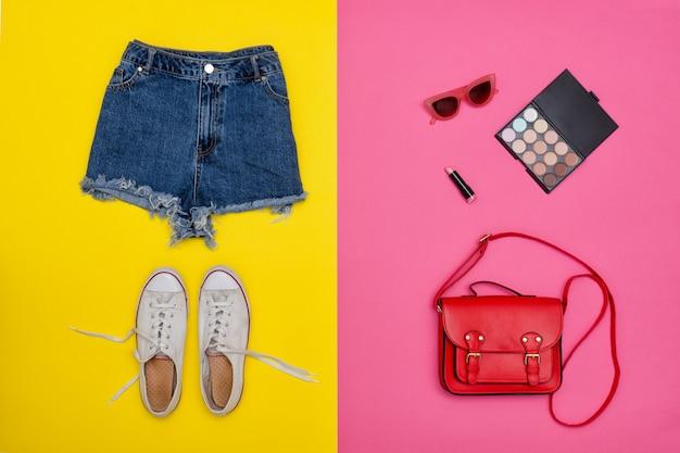 Short en jean, baskets blanches, sac à main rouge, cosmétiques. fond jaune et rose vif