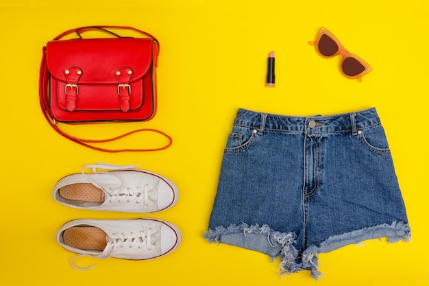 Short en jean, baskets blanches, sac à main rouge. fond jaune vif. concept à la mode