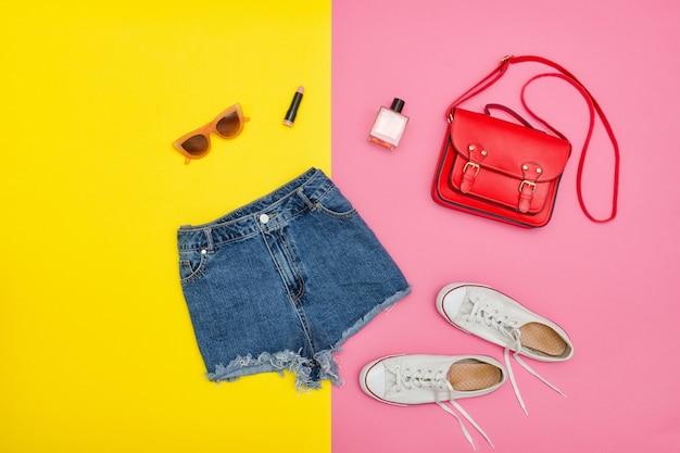 Short en jean, baskets blanches, sac à main rouge, lunettes de soleil. mur jaune et rose vif. concept à la mode
