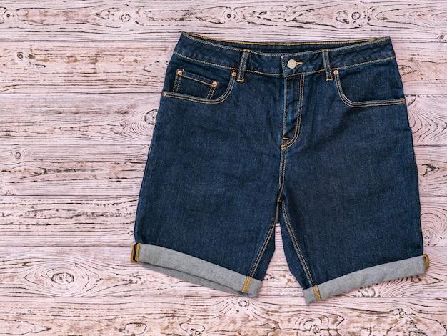 Short en jean bleu sur une surface en bois rose teinté