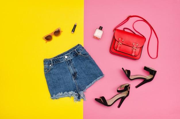 Short en jean, chaussures noires, sac à main rouge, lunettes de soleil. fond jaune et rose vif. concept à la mode