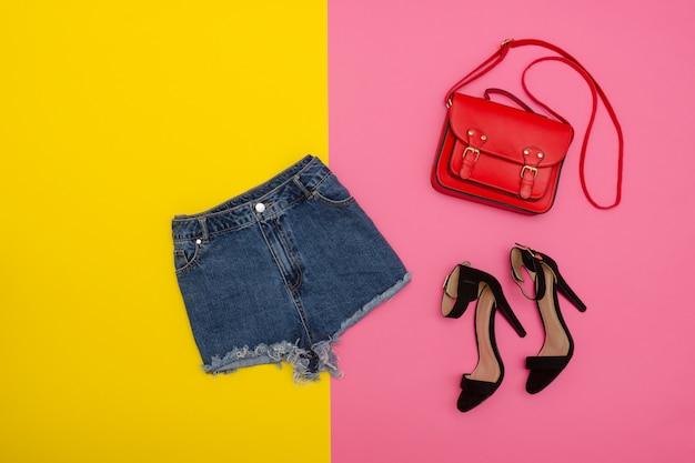 Short en jean, chaussures et sac à main rouge, fond jaune et rose vif.