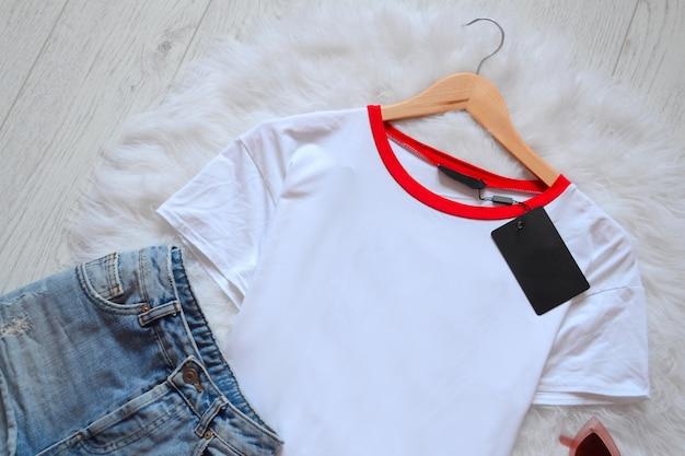 Short en jean court et un t-shirt blanc sur le nouveau trempel sur fourrure blanche. vue d'en-haut