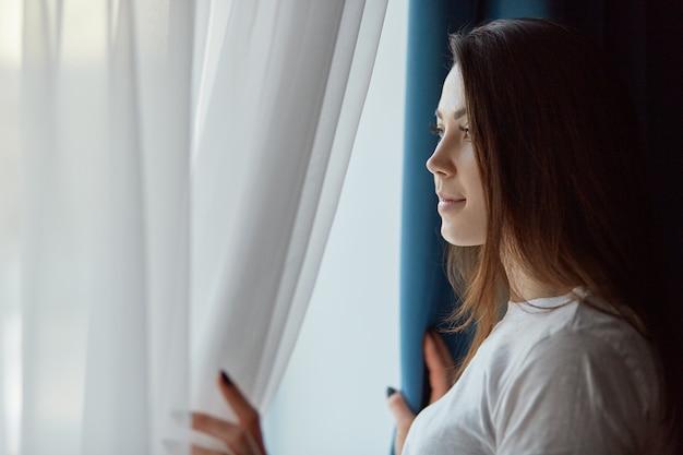 Shot horizontale de jolie brune pensive jeune femme en t-shirt blanc décontracté, regarde par la fenêtre avec une expression réfléchie