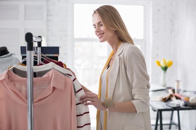 Showroom branché. jolie jolie femme d'affaires calculant le vêtement sur le stand en souriant