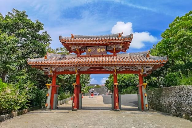 Shureimon gate dans le château de shuri à okinawa, japon avec ciel bleu. la tablette en bois qui orne la porte comporte des caractères chinois qui signifient «terre de propriété»