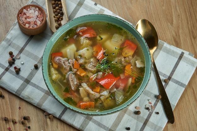Shurpa - une soupe traditionnelle, épaisse et nutritive du caucase. soupe d'agneau appétissante avec tomates, poivrons, oignons et pommes de terre dans un bol bleu. fermer