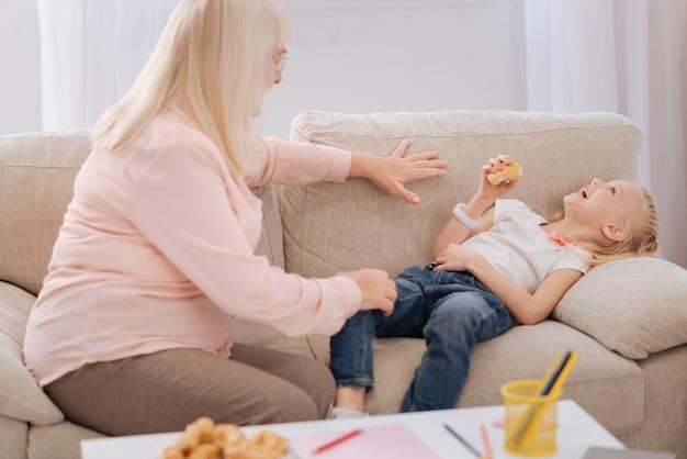 Si amusant. joyeuse fille blonde ravie tenant un cookie et riant en position couchée sur le canapé