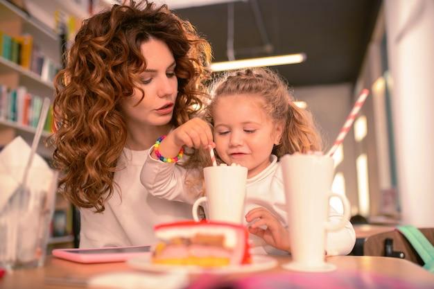Si savoureux. femme brune sérieuse à la recherche de côté tout en parlant à son enfant