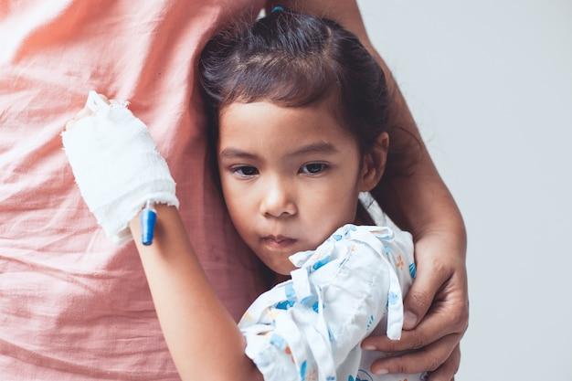 Sick asian petite fille fille qui a une solution iv bandée étreignant sa mère