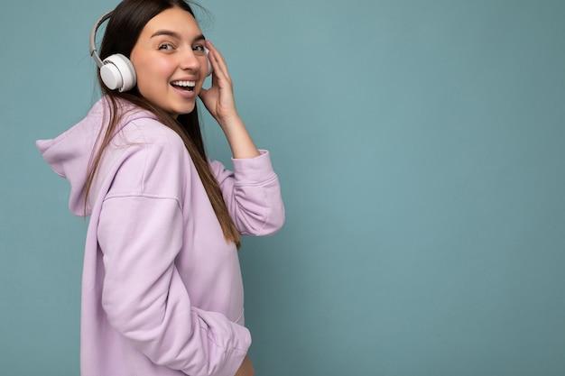Sideprofile belle jeune femme brune souriante et heureuse portant un sweat à capuche violet clair