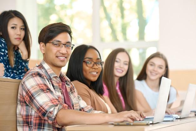 Sideview des coéquipiers regardant la caméra assis à l'université.