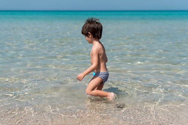 Sideview, garçon, plage, jouer, eau