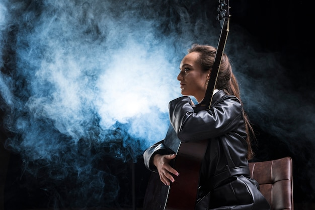 Sideways woman hugging the guitar and stage smoke