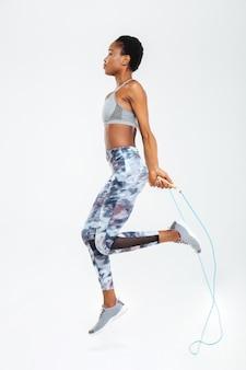 Sied vue portrait de femme sautant sur une corde à sauter isolée sur un mur blanc