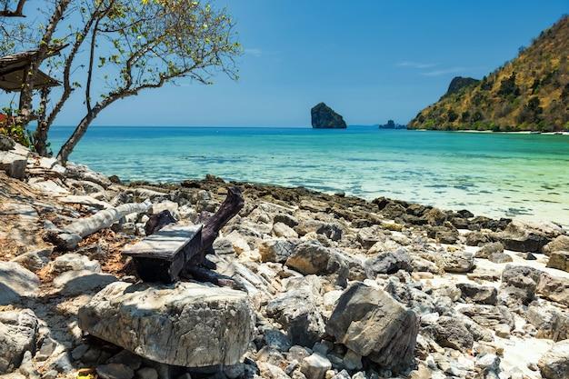Siège en bois par andaman sea shore pour se reposer et voir l'océan marin à thale waek, krabi, thaïlande. célèbre destination estivale après le verrouillage du covid-19.