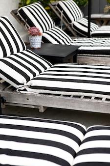 Sièges en bois avec coussins à rayures noires et blanches