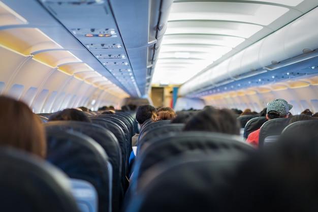 Sièges dans l'avion et passagers assis dans toute la zone en attente de l'avion décollant de la piste.