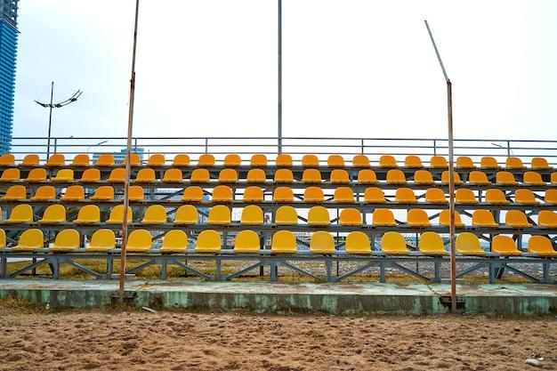 Sièges en plastique jaune sur le podium d'un petit terrain de sport.