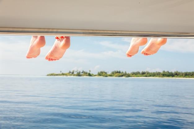 Sièges de première classe. gros plan des pieds d'enfants au pont supérieur du bateau surplombant la vue sur l'océan sur fond de mer de vacances.