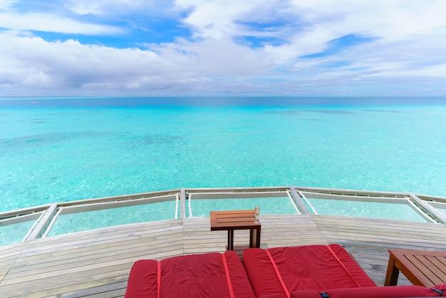 Sièges rouges et boisson fraîche sur le balcon avec vue sur la mer turquoise cristalline par une belle journée