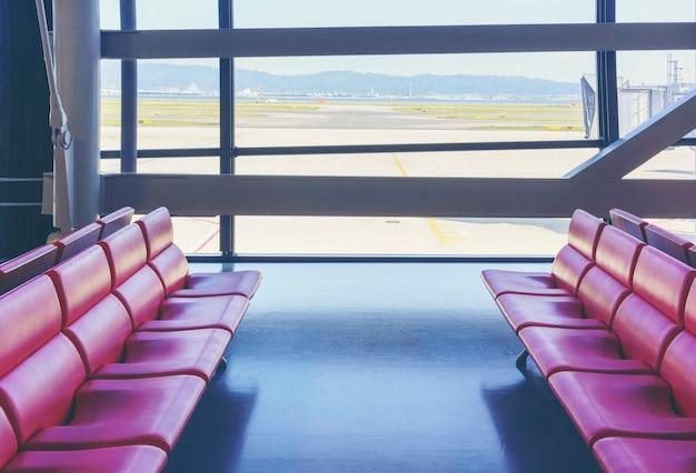 Sièges rouges vides à la porte du terminal de l'aéroport international regardant de beaux paysages de la ville depuis la fenêtre en verre