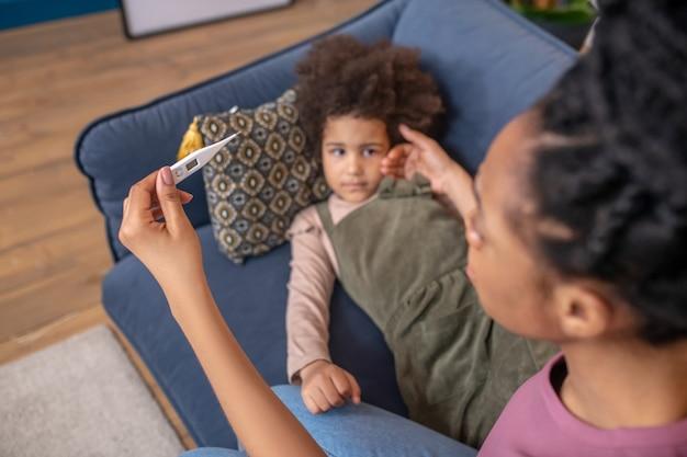 Signal d'alarme. thermomètre électronique avec la main d'une femme à la peau foncée alarmée assise près d'une petite fille triste et allongée à la maison