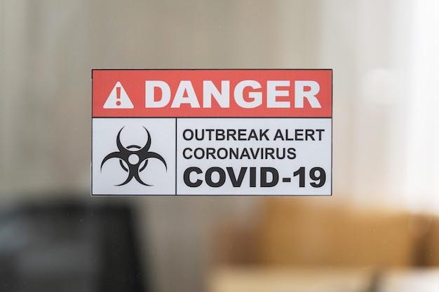 Signalisation d'avertissement covid-19 sur la porte du miroir de l'hôpital