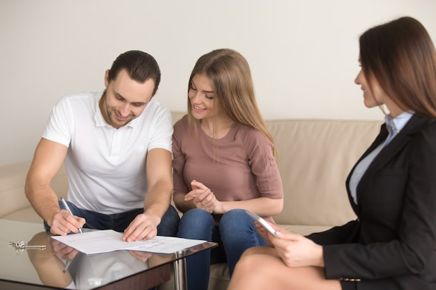 Signature d'un accord de réunion avec un agent immobilier, un couple achetant un appartement loué