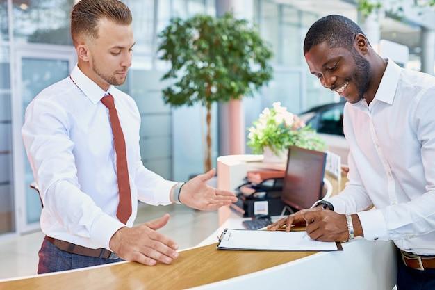 Signature d'un contrat client africain chez un concessionnaire automobile