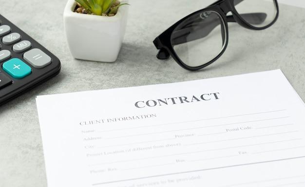 Signature du contrat légal avec calculatrice et lunettes