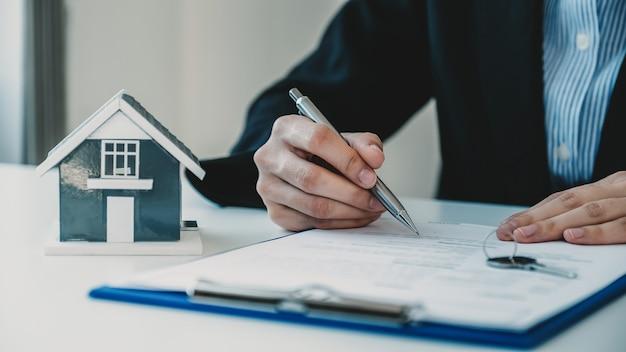 Signature du contrat à la main après que l'agent immobilier explique le contrat commercial à l'acheteur