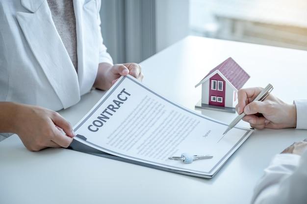 Signature du contrat à la main après que l'agent immobilier explique le contrat commercial, le loyer, l'achat, l'hypothèque, le prêt ou l'assurance habitation à l'acheteur