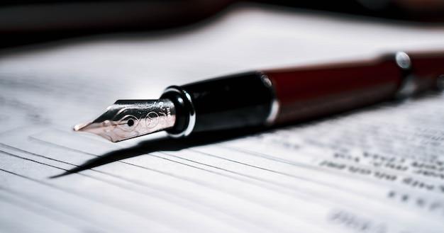 Signature du document contractuel avec stylo plume, gros plan.