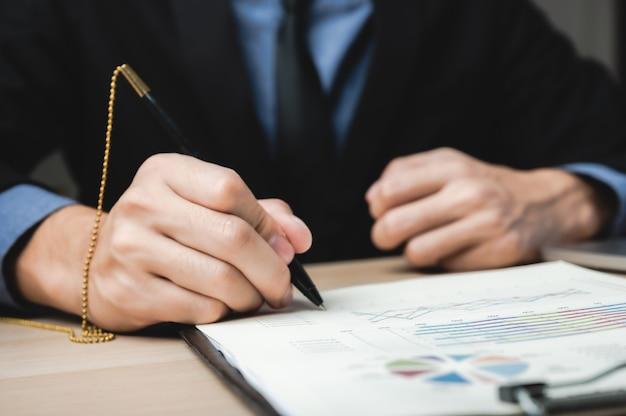 Signature à la main signer le contrat commercial approuvé pour certifier et autoriser sur le document papier