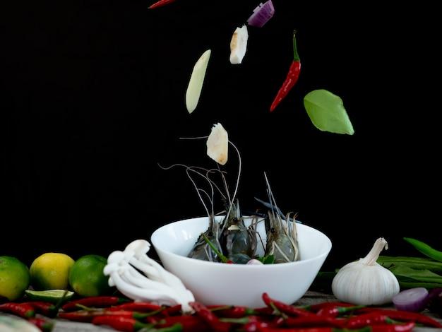 Signature thailand food, soupe tom yum goong aux épices et ingrédients sur fond noir