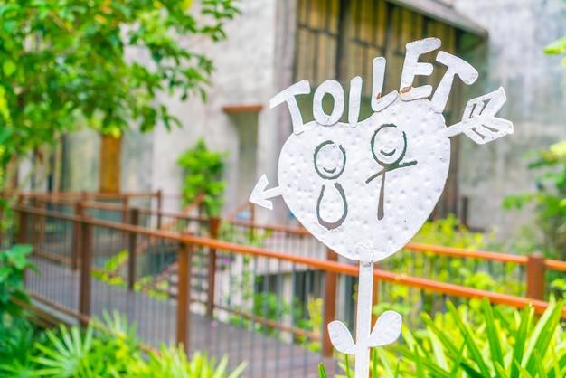 Un signe accroché à l'entrée d'un toilette.