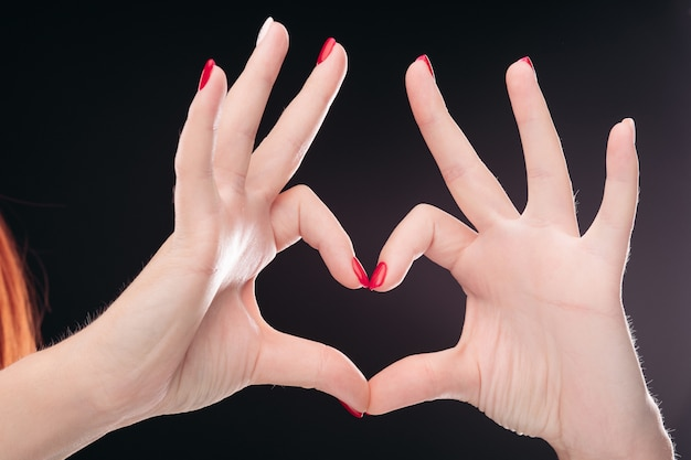 Signe d'amour fait à la main avec des ongles manucurés rouges sur fond noir