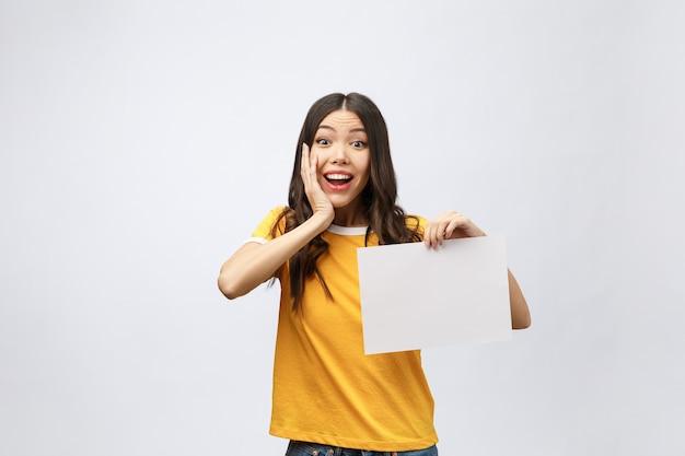 Signe de bannière publicitaire - femme excitée pointant vers le bas sur du papier d'affichage vide vide