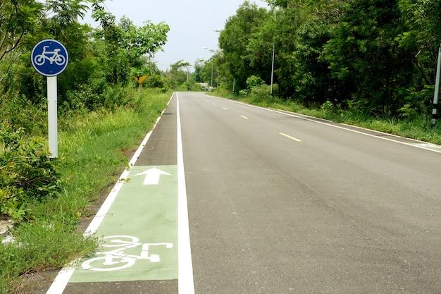 Signe bleu de la voie cyclable et ligne de signaux verts sur la route de campagne