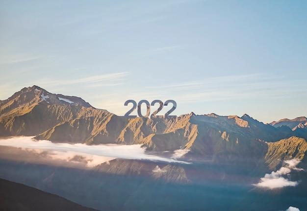 Un signe de bonne année 2022 au sommet de la montagne avec coucher de soleil, symbole de nouveaux succès et opportunités