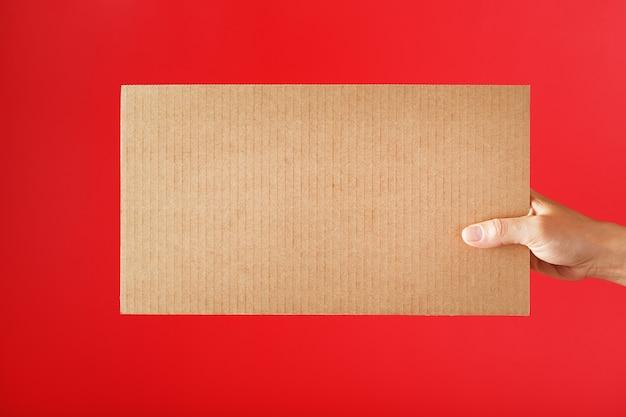 Signe de carton à disposition sur une surface rouge avec l'espace libre
